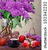 Still life with huge bunch of lilac and tulip, cup and red apple - stock photo