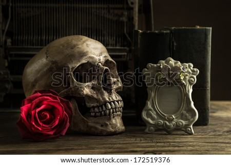 Still life with human skull with red rose, old book and telephone on wooden floor - stock photo