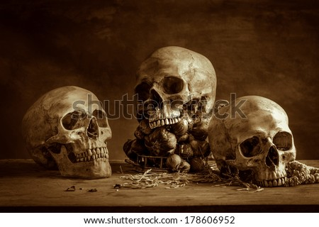 Still life with human skulls and bunch of garlics on wooden table - stock photo