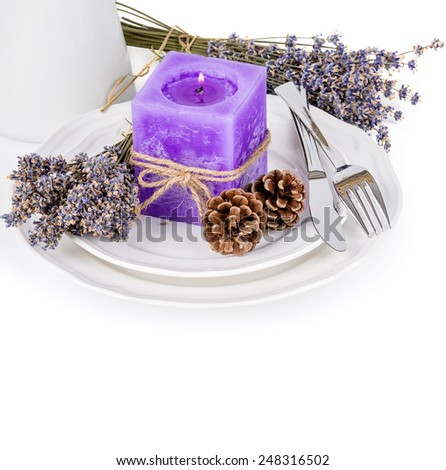 Still life with lavender candle, fir cones and dry lavender on a white plate isolated on white - stock photo
