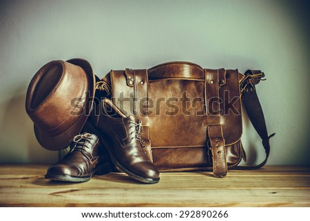 Still life with leather suitcase, brown shoes, and old glasses on the book, vintage style - stock photo