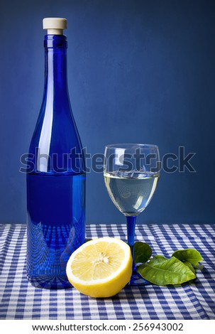 Still life with lemon and blue bottle over grunge blue wall - stock photo