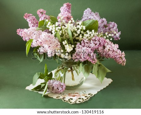 Still life with lilac flowers and lily of the valley in vase isolated on artistic background - stock photo