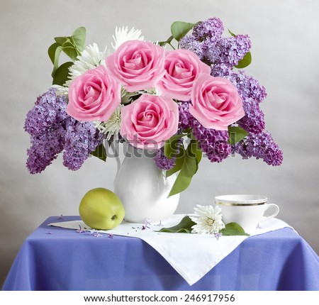 Still life with lilac flowers, roses, apple and cup  - stock photo