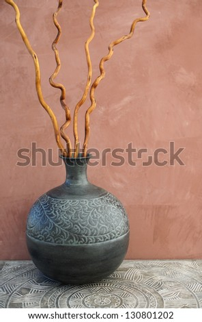 Still life with metal vase, wood, table, clay wall, and twisted willow branches.