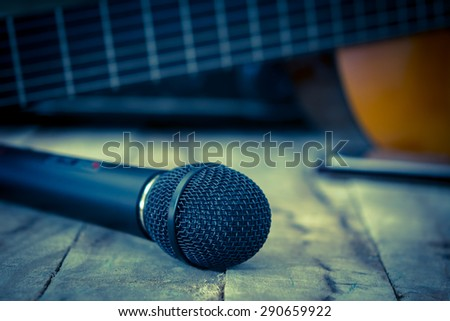 Still life with Microphone and classic guitar waiting on wooden floor, vintage style - stock photo