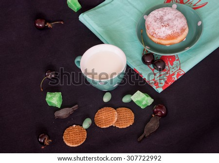 Still life with milk, cherries, cookies and wooden birds on  black background - stock photo