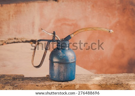 Still life with oil can on brick blur background - stock photo