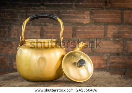 still life with old brass kettle brick background - stock photo