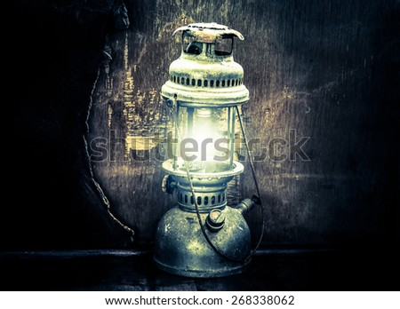 Still life with old lamp on wood,Light lamp in dark ,vintage filters effects - stock photo
