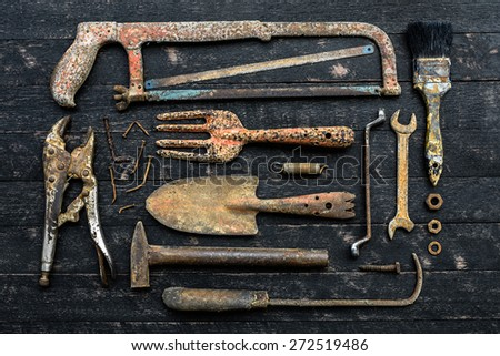 Still life with old rusty tools on wood board background - stock photo