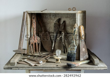 Still life with old rusty tools on wood table with cement wall background - stock photo