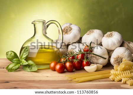 still life with olive oil,vegetables on wood table - stock photo
