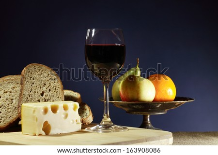 Still life with one goblet of red wine near sliced bread and cheese - stock photo