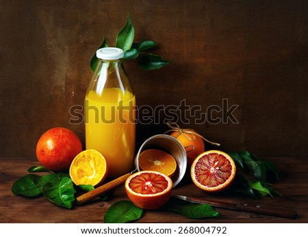 Still life with orange fruit and juice in glass bottle on wooden table. Painting style.  - stock photo