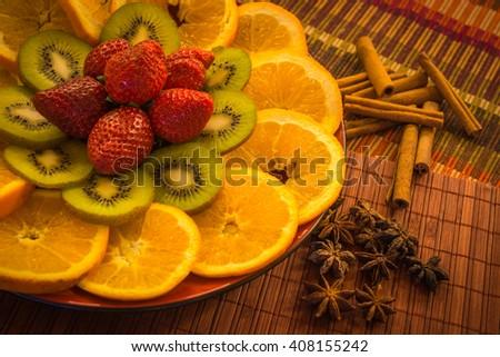 Still life with oranges, kiwi, strawberry, cinnamon and anise - stock photo