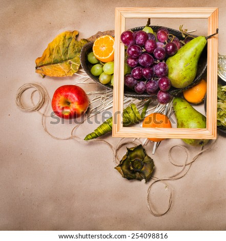 Still life with pears, apple, grapes, tangerines, physalis with leafs, twine, decorations, empty wooden frame and silver bowl on light brown paper. View from the top - stock photo