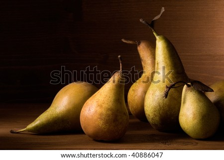 still life with pears on wooden table over an wooden wall - stock photo