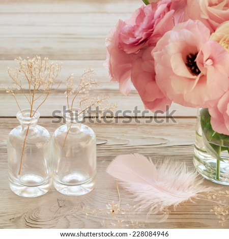 Still life with pink flowers in a vase with feather and two glass botles - vintage look - stock photo