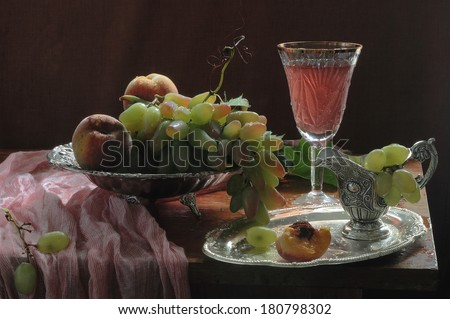 Still-life with pink wine in a crystal glass and fresh fruit, fresh appetizing juicy peaches and clusters of ripe grapes in a vase for fruit and invigorating pink wine in a wine glass on a long leg - stock photo