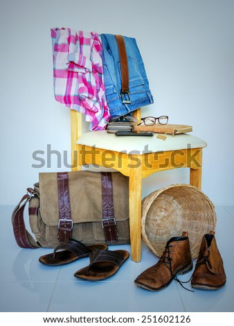 still life with plaid shirt, accessory, and jeans on wooden chair over grunge background, casual vintage style. - stock photo
