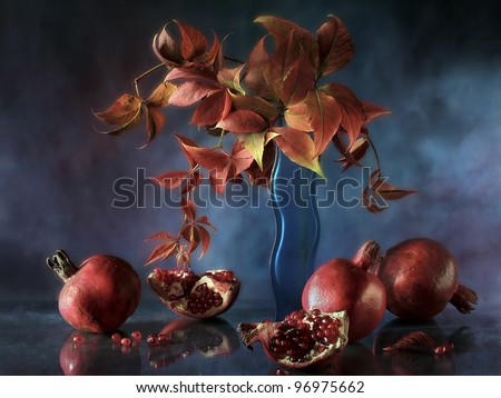 still life with pomegranates and vine leaves - stock photo
