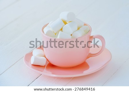 Still life with porcelain pink cup full of white marshmallows - stock photo