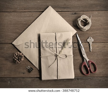 still life with postal parcel wrapped in brown paper and the contents of a workspace composed. Different objects on wooden table. sepia filter effect.Flat lay , - stock photo
