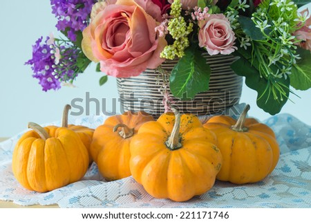 Still life with pumpkin and flowers on wooden table - stock photo