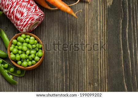 Still life with raw carrots, green peas and red twine on dark wooden table. Copyspace  - stock photo