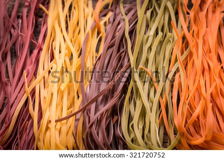 still life with raw homemade pasta and ingredients for pasta.natural dyes for pasta (tomato, spinach, carrots,beet) - stock photo