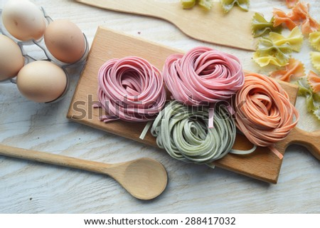 still life with raw homemade pasta and ingredients for pasta.process of cooking pasta.natural dyes for pasta (tomato, spinach, carrots),ingredients for homemade pasta(flour, eggs, water)