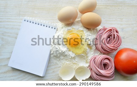 still life with raw homemade pasta and ingredients for pasta.process of cooking pasta.natural dyes for pasta (tomato, spinach, carrots),ingredients for homemade pasta(flour, eggs, water)recipe book - stock photo