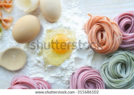 still life with raw homemade pasta and ingredients for pasta.process of cooking pasta.natural dyes for pasta (tomato, spinach, carrots),ingredients for homemade pasta(flour, eggs, water) - stock photo