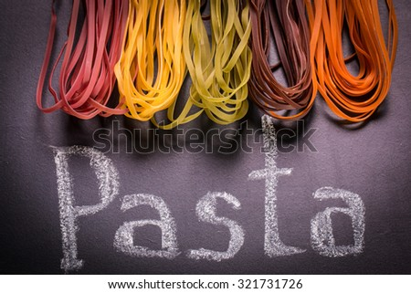 still life with raw homemade pasta and ingredients for pasta.process of cooking pasta.natural dyes for pasta (tomato, spinach, carrots,beet) - stock photo