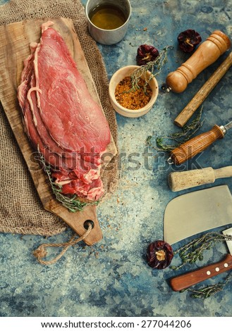 Still life with raw steaks over on vintage cutting board with kitchen tools. Rustic tools.  Toned image. - stock photo