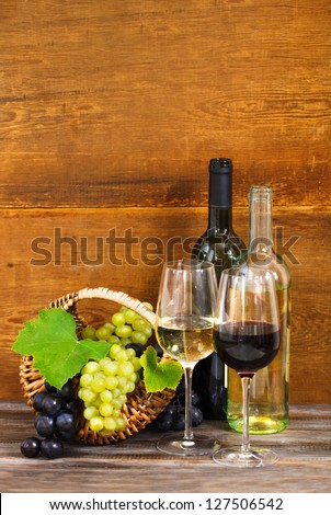 Still life with red and white wine, bottles and basket with grapes