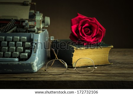 Still life with red rose bud on old book near typewriter and glasses - stock photo