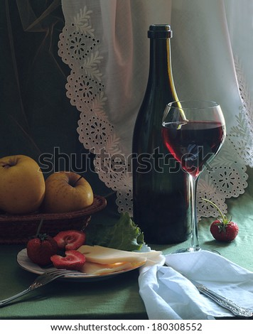 Still-life with red wine a fresh strawberry and apples and cheese, fragrant red wine in a graceful glass and juicy apples in a wattled vase and a fresh strawberry with cream cheese on a plate - stock photo