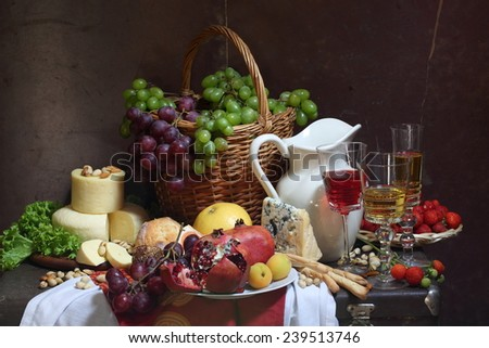 Still-life with red wine, a strawberry, a pomegranate, grapes and cheese - stock photo