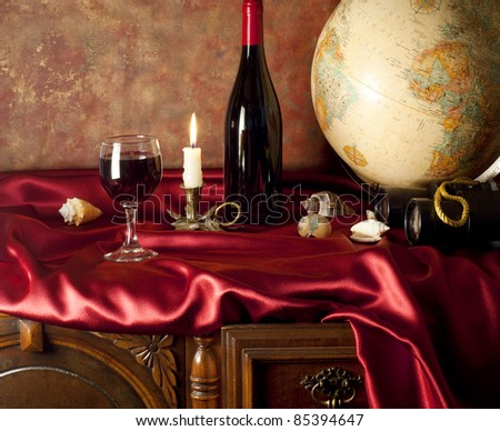 Still-life with red wine and globe - stock photo