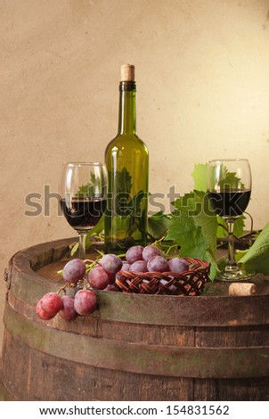 still life with red wine, bottle, glass and old barrel