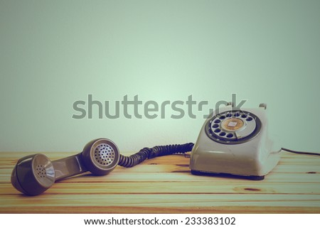 Still life with retro phone on wooden table over grunge background - stock photo