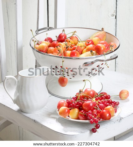Still-life with ripe fruit and berries, a juicy sweet sweet cherry both appetizing juicy pears and a red currant and a beautiful small jug  - stock photo