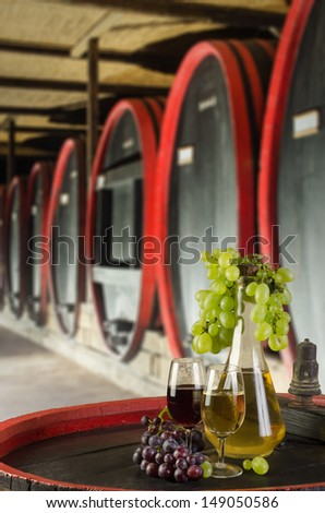 Still life with ripe grapes, wine glasses and wine bottles in old cellar - stock photo
