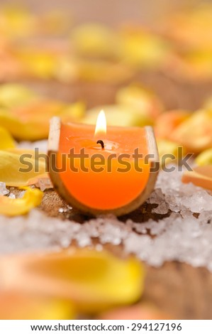 Still life with rose petals with candle ,pile of salt isolated on old wood