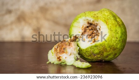 still life with rot guava on wooden table - stock photo