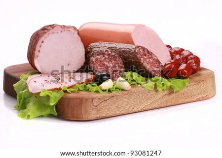 Still Life with sausages, salami and ham on a wooden table isolated on white background. - stock photo