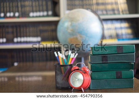 "Still life with school books  against blackboard with ""library book"" on background - stock photo"