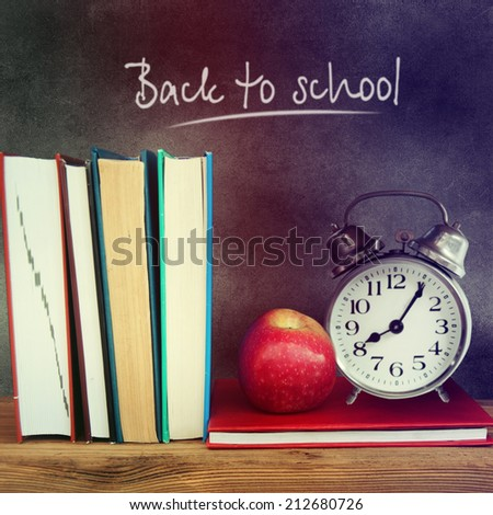 """Still life with school books and apple against blackboard with """"back to school"""" on background. - stock photo"""
